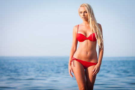 Sexy blond girl in red bikini posing on a beach 版權商用圖片