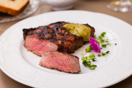 new york strip: New York steak with herb butter on a plate
