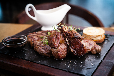 Mixed grilled meat platter. Assorted delicious grilled steaks served with goat cheese on warm dish. Stock Photo