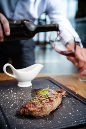 new york strip: New York steak with waiter pouring red wine on background