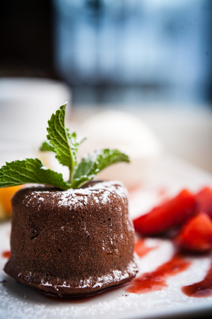 Chocolate fondant with a scoop of mint ice cream and cherry sauce
