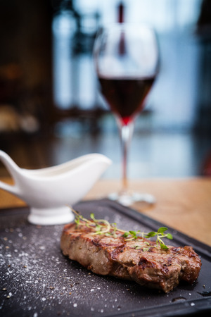 new york strip: New York steak with glass of red wine