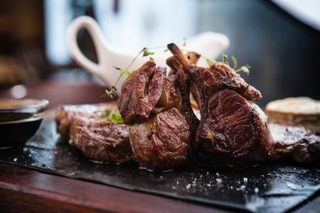 carne asada: Mezclado plato de carne a la parrilla. Surtido de deliciosas carnes a la parrilla servido con queso de cabra en el plato caliente. Foto de archivo