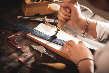 Leather handbag craftsman at work in a workshop Reklamní fotografie - 62612778