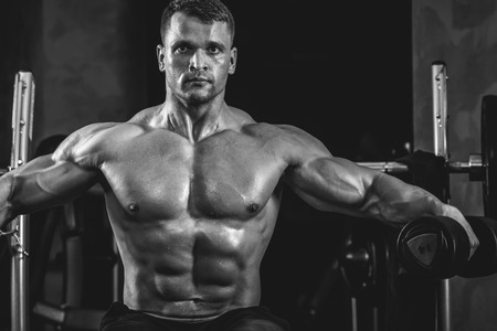 man gym: Brutal athletic man pumping up muscles with dumbbells in monochrome