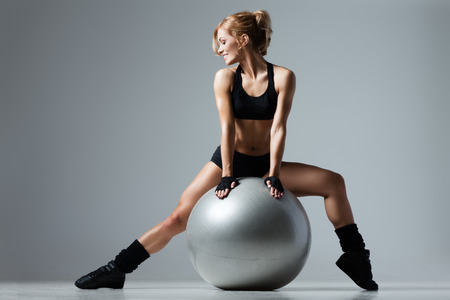 Athletic woman sitting on a gym ball on gray background