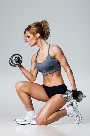 athletics: Smiling athletic woman pumping up muscles with dumbbells on gray background