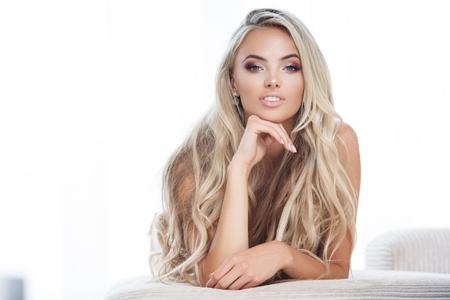 Portret van aantrekkelijke blonde glimlachende vrouw in het wit Stockfoto
