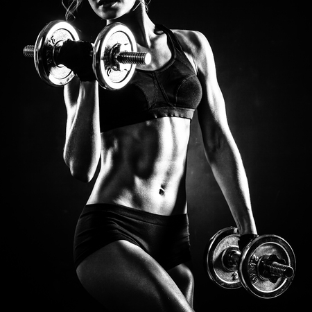 Brutal athletic woman pumping up muscles with dumbbells Фото со стока