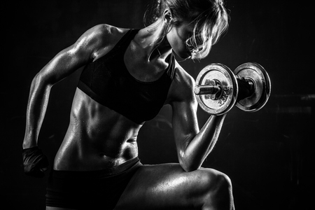 Brutal athletic woman pumping up muscles with dumbbells Banco de Imagens - 62517831