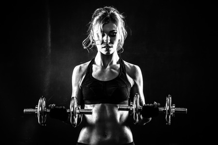 Brutal athletic woman pumping up muscles with dumbbells Banque d'images