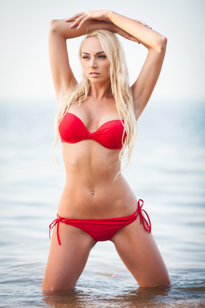sexy girl posing: Sexy blond girl in red bikini posing on a beach Stock Photo