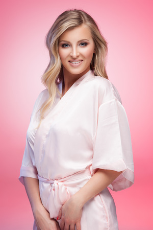 bath robes: Young smiling blond lady wearing a sexy bathrobe on pink background Stock Photo