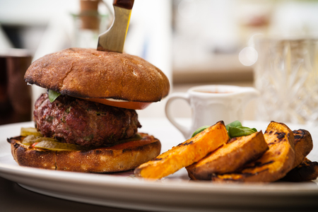 beefburger: Beefburger with fried sweet potatoes served on a white plate