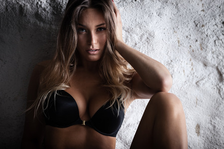 sexy nude blonde: Fashion portrait of beautiful female model posing in black lingerie near white wall