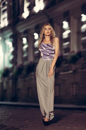 Bella signora in abito lungo che propone nella città di notte