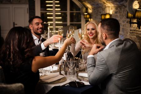 Cuatro amigos con los vidrios de champange celebrando y tostado en el restaurante