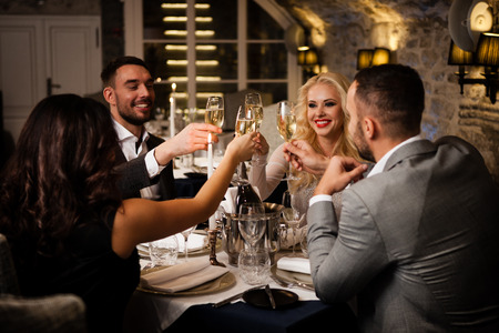 Four friends with champange glasses celebrating and toasting in restaurant Banco de Imagens