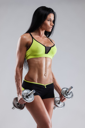 athletics: Athletic woman pumping up muscles with dumbbells on gray background