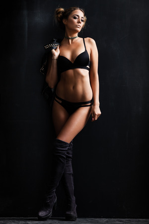 Young woman in black lingerie posing near black wall
