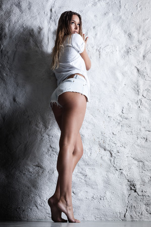 shorts t shirt sexy: Portrait of a young sexy lady in t-shirt and jeans shorts posing near white wall Stock Photo