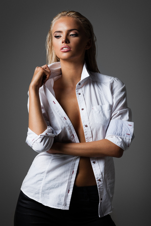 sexualidad: hairstyle, sexuality and fashion concept - portrait of a natural beautiful blond woman in white shirt with wet hair on grey background Foto de archivo