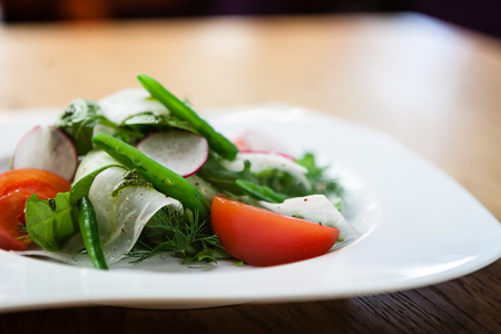 fresh salad of tomatoes, raddish and cucumber and on a plate Stock Photo