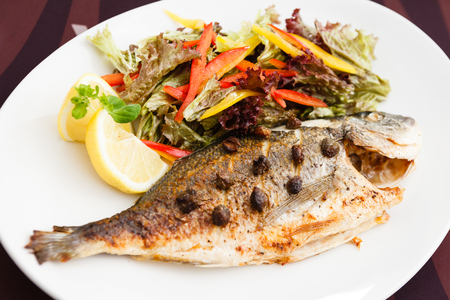 Grilled gilt-head bream fish in herbs and lemon Stock Photo