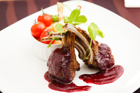 Grilled lamb served with cranberry sauce tomatoes and potato garnish Stock Photo