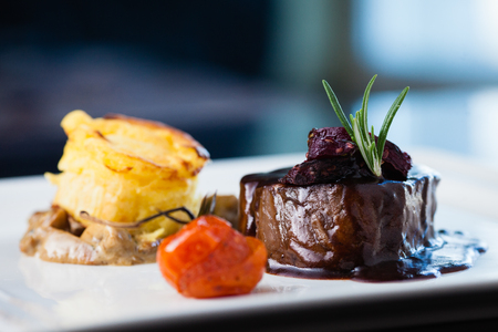 Roasted beef tenderloin with herb-potato muffin, mushroom ragout, baked tomatoes and rosemary-currant sauce Stock Photo