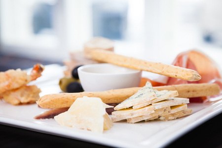 Tapas platter with variety of cheeses, ham and olives