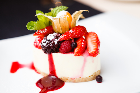 Cheesecake with wild berries on white plate Stock Photo