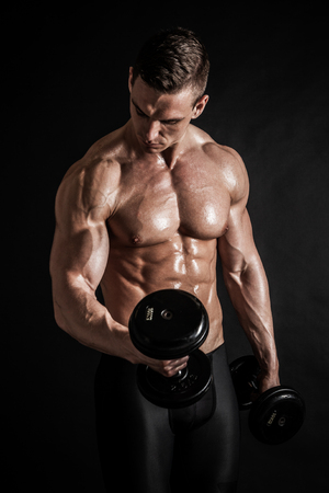 Athletic shirtless young male fitness model with dumbbells Stock Photo - 116350282