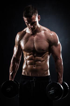 Athletisches hemdloses junges männliches Fitnessmodell mit Hanteln