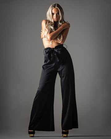fashionable young woman in trousers posing on grey Stock Photo - 117502007