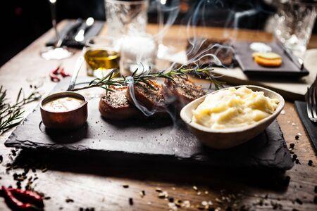 Pork tenderloin served on a board in restaurant Imagens