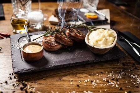 Pork tenderloin with mashed potatos, bacon and mustard sauce covered with a branch of smoking rosemary Stock Photo