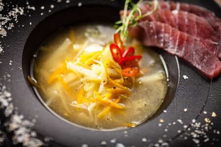 Clear Fish soup served in a bowl in restaurant