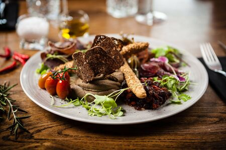Meat platter for two: Dry-aged beef brisket, dry-aged duck fillet, beef liver pate, dry-aged lamb striploin, cranberry jam and grissini Stock Photo