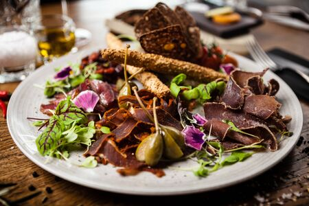 Meat platter for two: Dry-aged beef brisket, dry-aged duck fillet, beef liver pate, dry-aged lamb striploin, cranberry jam and grissini 스톡 콘텐츠