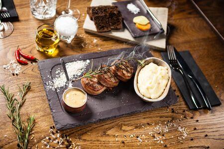 Pork tenderloin served on a board in restaurant Stock Photo