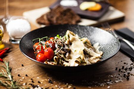 Black Angus Pasta served in a black bowl in restaurant Stock Photo