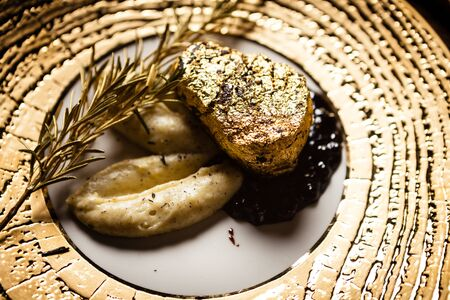 Black Angus tenderloin steak covered with 24 carat gold, potato puree, red wine sauce with berries, rosmarine Фото со стока