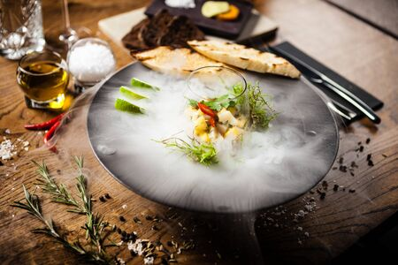 Scallop ceviche served in black bowl with liquid ice smoke