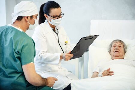 healthcare in hospital concept. two doctors making medical examination of old lady