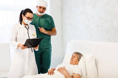 healthcare in hospital. male surgeon and female doctor or nurse making medical examination of old lady lying in bed and getting treatment