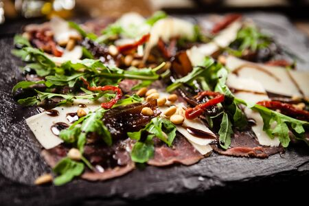 Beef carpaccio served on a board. Delicious healthy Italian traditional antipasti snacks closeup served for lunch with wine in modern gourmet restaurant.
