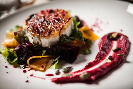 Grilled goat cheese salad Pickled beetroot pumkin, cranberry jam, pumkin seeds Delicious mediterranean traditional vegeterian food closeup served for lunch in modern cuisine gourmet restaurant
