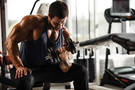 Fitness in gym, sport and healthy lifestyle concept. Handsome athletic man in blue shirt making exercises. Bodybuilder male model training biceps muscles with dumbbell. Banco de Imagens - 150582617