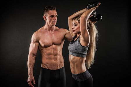 Fitness in gym, sport and healthy lifestyle concept. Couple of athletic man and woman showing their trained bodies on black background. Two bodybuilder models standing and demonstrating tight muscles. Foto de archivo